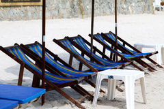 Umbrellas and deckchairs against of seascape under blue sky Stock Photos