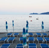 Umbrellas and deckchairs in Rapallo seaside resorts at sunset. Rapallo area is included in the Parco Naturale Regionale di Portofi Stock Photography