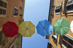 Umbrellas of different colors over the street with blue sky as background Stock Photo