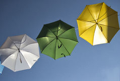 Umbrellas of different colors over the street with blue sky as background Royalty Free Stock Photography