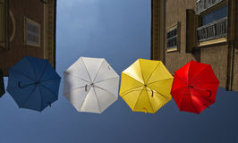 Umbrellas of different colors over the street with blue sky as background Stock Images