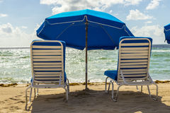 Umbrellas and empty beach couches Stock Photos