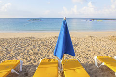 Umbrellas and empty beach couches. At the beach in morning light Royalty Free Stock Photo
