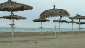 Umbrellas on empty beach. Waves splashing in stormy sea. Off-season at resort. Stock footage stock video