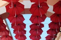 Umbrellas flying in sky over city street  in Venice. Lots of red umbrellas flying in sky over city street  in Venice, Italy Stock Images