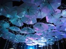 Umbrellas hanging above the black sky. stock photos