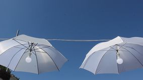Umbrellas hanging with light in the middle stock video footage