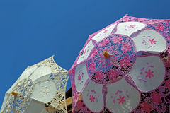 Umbrellas with lace in pink and white. Umbrellas with lace, in pink and white, on a background with sky Royalty Free Stock Images