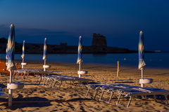 Umbrellas lined up on the beach. Umbrellas and deckchairs lined up neatly ready for a full day of sunbathing. Sfinale tower visible in the background Royalty Free Stock Images