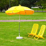 Umbrellas and loungers standing on the grass. Yellow umbrellas and loungers standing on the grass royalty free stock photography