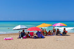 Umbrellas. People sitting under the umbrellas on a beach in western Peloponnese, Greece Royalty Free Stock Photo