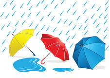 Umbrellas in the Rain. Yellow blue and red umbrellas lying in a puddle Royalty Free Stock Photos