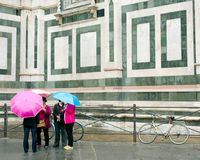 Umbrellas in the Rain, Florence, Italy. Tourists huddle outside the Duomo cathedral in Florence, Italy as the rain washes down Royalty Free Stock Images
