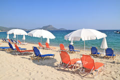 Umbrellas and recliners by the sea Stock Photography