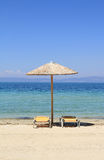 Umbrellas and recliners by the sea Royalty Free Stock Photos
