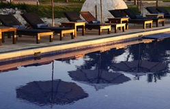 Umbrellas Reflected. Calm morning at the beach side pool Royalty Free Stock Images