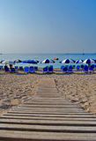 Greek beach with umbrellas. Umbrellas for rent,Greek sandy beach with boardwalk Royalty Free Stock Photos