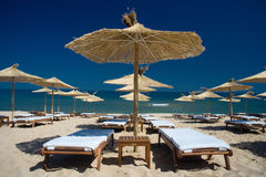 Umbrellas row on the sea shore. Perfect sea holiday view with sun umbrellas and chairs Stock Images