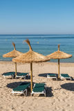 Umbrellas and seats on a beach. Mallorca summer beach with umbrellas and seats with blue sky as background Royalty Free Stock Photo