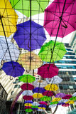 Umbrellas sheltering people from the rain in world square Royalty Free Stock Image