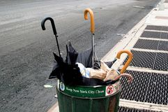 Umbrellas on the street of New York city in America. New York is a city located in east coast of United States. It looks like they are in the trash bin royalty free stock photos