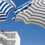 Umbrellas in style of greek flags. Stock Photo