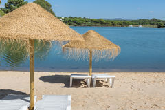 Umbrellas and sun loungers on beach near the lake. Summer vacation. Royalty Free Stock Photo