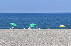 Umbrellas and Sunbeds on the beach Royalty Free Stock Images