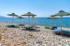 Umbrellas and sunbeds at stony beach of Paleochora town on Crete island Stock Images