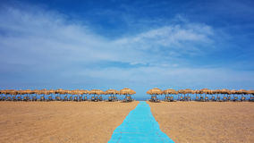 Umbrellas and sunbeds on sunny empty beach Stock Photo