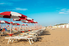 Umbrellas and sunlongers on the sandy beach. Red and white umbrellas and sunlongers on the sandy beach in Italy Royalty Free Stock Images