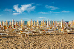 Umbrellas and sunlongers on the sandy beach. Withdrawn yellow umbrellas and sunlongers on the sandy beach in Italy Royalty Free Stock Image