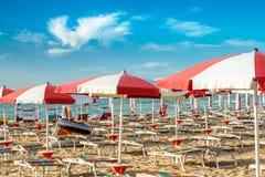 Umbrellas and sunlongers on the sandy beach. Red and white umbrellas and sunlongers on the sandy beach in Italy Stock Photos