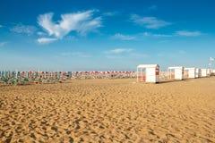 Umbrellas and sunlongers on the sandy beach. Red and white umbrellas and sunlongers on the sandy beach in Italy Royalty Free Stock Photo