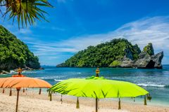 Umbrellas on a Tropical Beach and Islands in the Ocean. Indonesia. Sun umbrellas on the beach. Emerald water. Rocky island in the ocean, covered with jungle Royalty Free Stock Photo