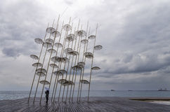 Umbrellas in the waterfront of Thessaloniki, Greece, under a cloudy sky Stock Image