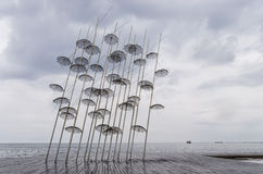 Umbrellas in the waterfront of Thessaloniki, Greece, under a cloudy sky Royalty Free Stock Photography