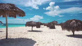 Umbrellas on the white sandy beach of Cayo Largo, Cuba. Azure water and white sand stock footage