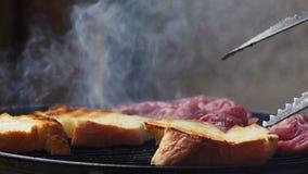 Umdrehen von Stücken Brot auf einem Grill stock footage
