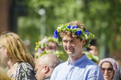 Umea, Sweden - June 21, 2019 Man in blue shirt enjoying swedish traditional mid summerday in a sunny day with colourful flower