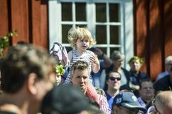 Beautiful swedish sweet happy woman is enjoying traditional decoration of mid summer day wearing colourful leave crown in sunny. Umea, Sweden - JUNE 23, 2017 royalty free stock photos