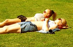 Two girls sunbathing in central park stock images