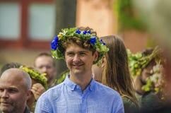 Umea Szwecja, mężczyzna w błękicie cieszy się szwedzki tradycyjny w połowie summerday w słonecznym dniu z colourful kwiat koroną, fotografia stock