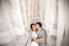 Umfassen Sie die jungen Paare am Hochzeitstag stockfoto