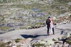 Umfassende jugendlich Alterstochter der Mutter, stehend auf Felsen w?hrend des Wanderns zum trolltunga, copyspace norwegen lizenzfreie stockbilder