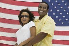 Umfassenfrau des Mannes, amerikanische Flagge im Hintergrund Stockfotografie