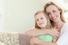 Umfassentochter der Mutter auf Couch Stockfoto