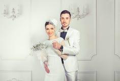 Umfassung der eleganten Braut und des Bräutigams stockfotografie