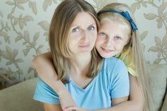 Umfassung der Mutter und ihres Familienporträts der jugendlichen Tochter Stockfotografie