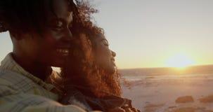 Umfassungsfrau des Mannes am Strand während des Sonnenuntergangs 4k stock footage
